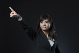 指を指すポーズをとるビジネス女性の写真素材 [FYI02969187]