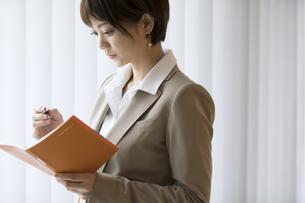 手帳を見るビジネス女性の写真素材 [FYI02969192]