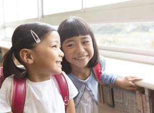 教室でランドセルを背負って笑う女の子2人の写真素材 [FYI02969195]