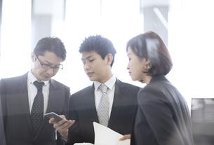 スマートフォンを見て打ち合わせをする3人のビジネス男女の写真素材 [FYI02969198]