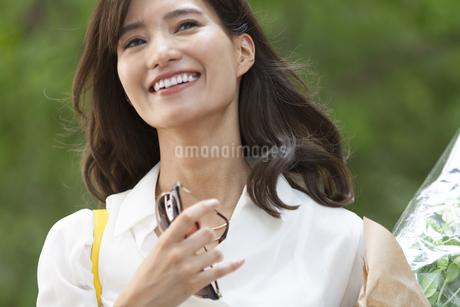 手にサングラスを持って笑う女性の写真素材 [FYI02969203]