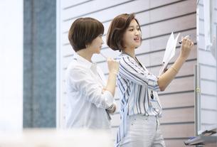 ホワイトボードを使って打ち合わせをする2人のビジネス女性の写真素材 [FYI02969212]