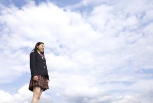 青空をバックに立つ女子高校生の写真素材 [FYI02969220]