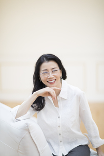 ソファーに座って微笑む女性の写真素材 [FYI02969222]