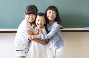 黒板の前で寄り添って笑う女の子3人の写真素材 [FYI02969224]