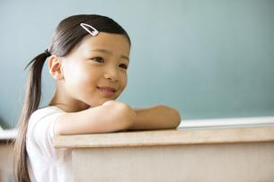 教卓の上に腕を置いて遠くを眺める女の子の写真素材 [FYI02969225]