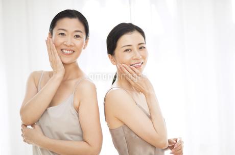 頬に片手を添えて微笑む2人の女性の写真素材 [FYI02969228]