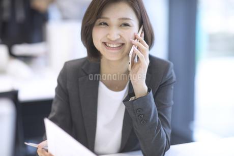 スマートフォンで通話するビジネス女性の写真素材 [FYI02969239]