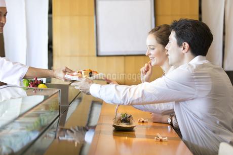 寿司を受け取る外国人の男女の写真素材 [FYI02969241]