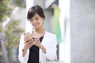 スマートフォンを操作するビジネス女性の写真素材 [FYI02969244]
