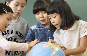 教室で地球儀を見る女の子4人の写真素材 [FYI02969248]