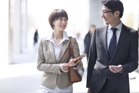 歩きながら打ち合わせをするビジネス男女の写真素材 [FYI02969257]