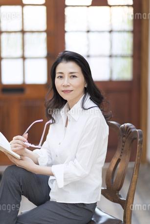 眼鏡と手帳を手に持って椅子に座る女性の写真素材 [FYI02969269]