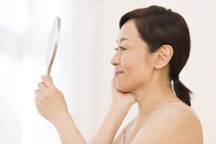 手鏡を見て微笑む女性の横顔の写真素材 [FYI02969274]