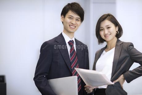 オフィスでカメラ目線で立つビジネス男女の写真素材 [FYI02969275]