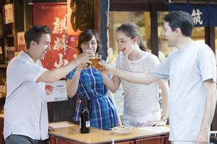 ビールで乾杯をする男女の外国人観光客の写真素材 [FYI02969276]