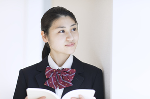 本を開き外を見つめる女子高校生の写真素材 [FYI02969289]
