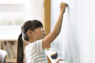 黒板に文字を書こうとする女の子の写真素材 [FYI02969292]
