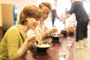 ラーメンを食べる男女の外国人観光客の写真素材 [FYI02969309]