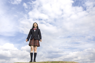 青空をバックに立つ女子高校生の写真素材 [FYI02969311]