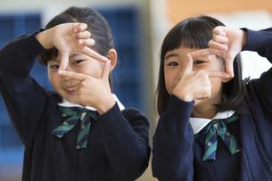 指でカメラのポーズをとる小学生の女の子2人の写真素材 [FYI02969317]