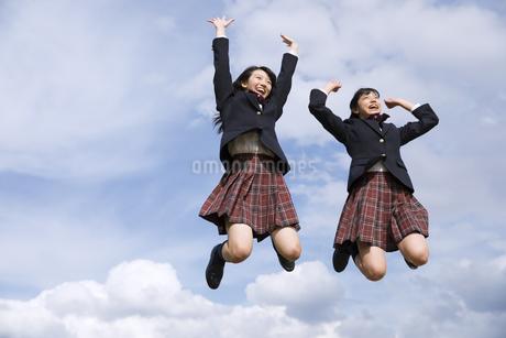 青空をバックにジャンプをする女子高校生たちの写真素材 [FYI02969323]