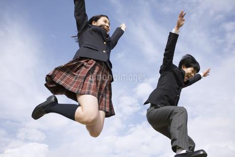 青空をバックにジャンプをする高校生たちの写真素材 [FYI02969324]