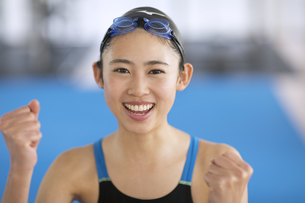 ガッツポーズで喜ぶ水着の女子学生の写真素材 [FYI02969340]