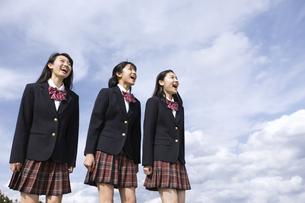 青空に叫ぶ女子高校生たちの写真素材 [FYI02969345]