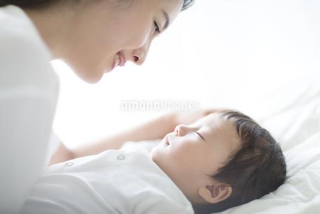 母親に見つめられながら眠る赤ちゃんの写真素材 [FYI02969346]