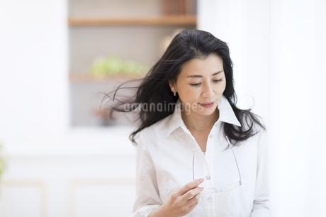 眼鏡を手に持ってうつむく女性の写真素材 [FYI02969347]