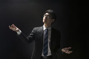 両手を広げ上を見上げるビジネス男性の写真素材 [FYI02969349]