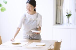 お皿をテーブルに置く女性の写真素材 [FYI02969355]