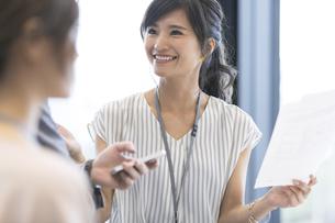 資料を持ち会話をするビジネス女性の写真素材 [FYI02969356]