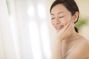 頬に片手を添えて目を瞑り微笑む女性の写真素材 [FYI02969361]