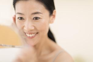 鏡の前でスキンケアをする女性の写真素材 [FYI02969362]