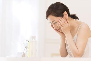 鏡の前でスキンケアをする女性の横顔の写真素材 [FYI02969371]