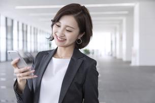 スマートフォンを操作するビジネス女性の写真素材 [FYI02969377]