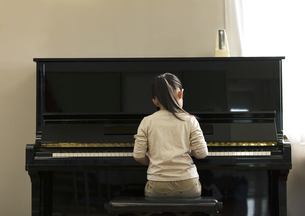 ピアノを演奏する女の子の後ろ姿の写真素材 [FYI02969400]