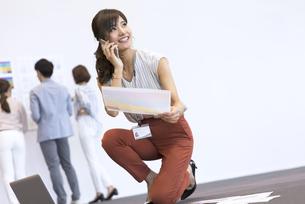 床に膝を置いて電話をするビジネス女性の写真素材 [FYI02969403]