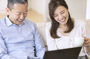 パソコンを見ながら会話をする夫婦の写真素材 [FYI02969404]