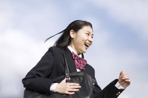 青空をバックに走る女子高校生の写真素材 [FYI02969416]