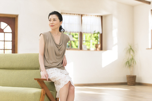 ソファーの肘掛けに腰掛ける女性の写真素材 [FYI02969422]