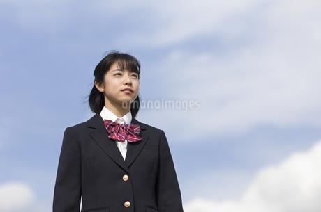 青空をバックに立つ女子高校生の写真素材 [FYI02969429]