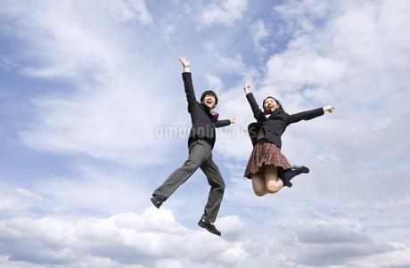 青空をバックにジャンプをする高校生たちの写真素材 [FYI02969430]