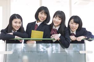 手すりに手を掛けカメラ目線の女子高校生たちの写真素材 [FYI02969436]