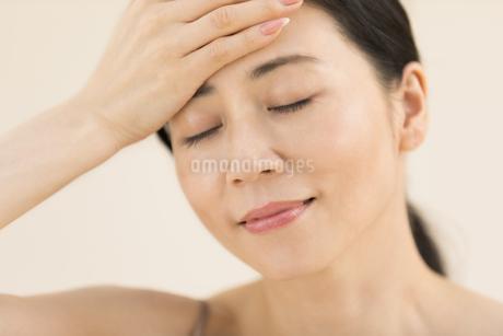 額に片手を添えて目を瞑る女性の写真素材 [FYI02969439]