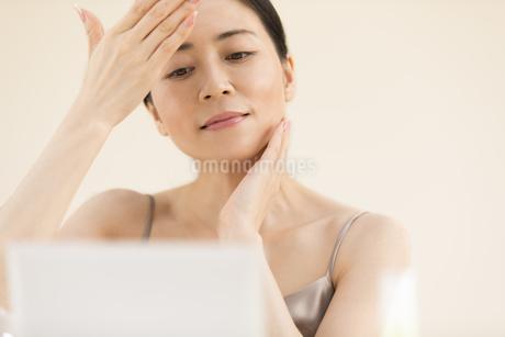 鏡の前でスキンケアをする女性の写真素材 [FYI02969446]