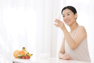 牛乳を手に微笑む女性の写真素材 [FYI02969450]