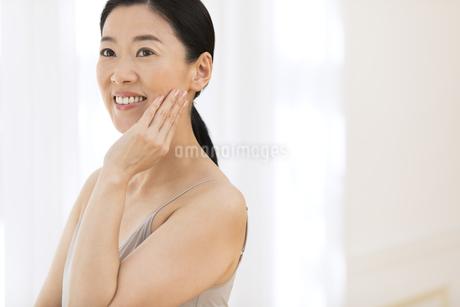 頬に片手を添えて微笑む女性の写真素材 [FYI02969451]
